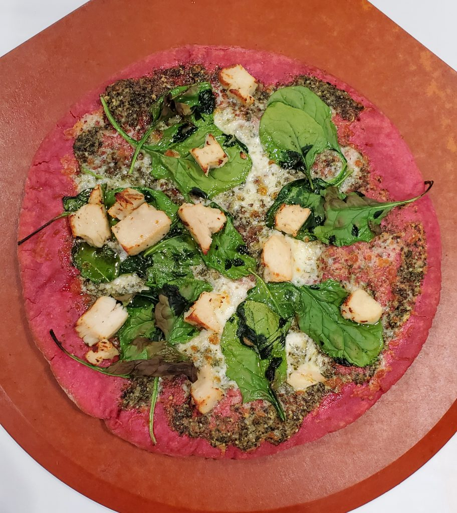 Beetroot pizza with chicken and spinach toppings on a wooden board
